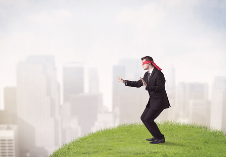 Young blindfolded businessman steps on  a patch of grass with a city in the background Stock Photo