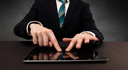 fulfil: Businessman in suit typing with dark background