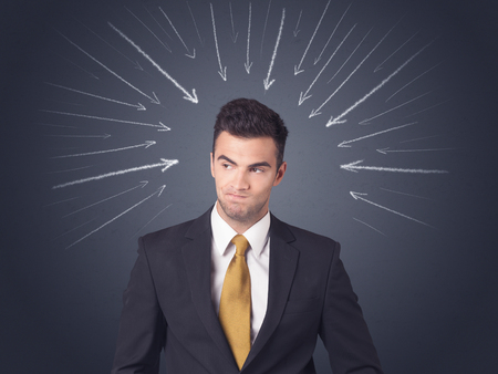 difficult decision: Young businessman with arrows pointing to his head
