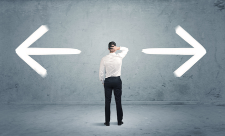 considerations: A businessman in doubt, having to shoose between two different choices indicated by arrows pointing in opposite direction concept