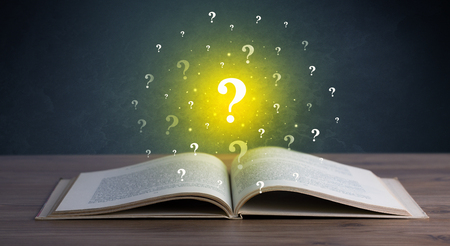 questioning: Yellow question marks hovering over open book Stock Photo