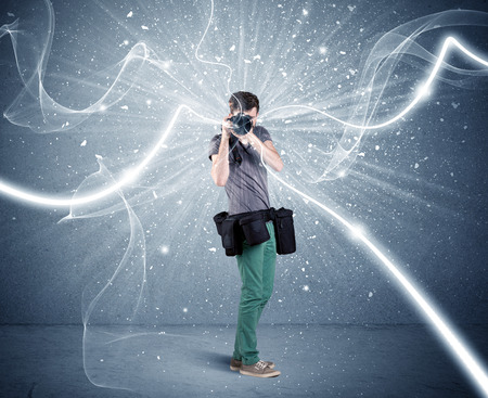 hands pocket: A young amateur photographer with professional photographic equipment taking picture in front of blue wall with dynamic white lines illustration concept Stock Photo