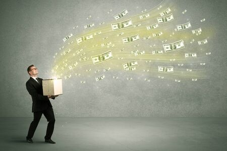 man flying: Successful young sales person making a lot of money concept illustrated with euro dollar bills flying out of a box held in his hand.