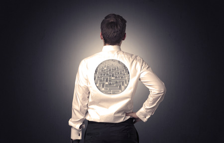 Businessman standing and thinking with maze graphic on his back