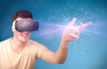 thoughtful: Young impressed man wearing virtual reality goggles with blue circles around his finger Stock Photo