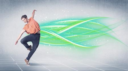 Un buen aspecto fresco baile del bailarín de la calle en frente de fondo gris con blanco y brillante, colorido líneas verdes concepto