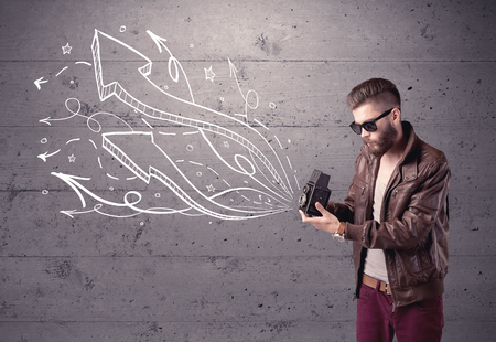 smile close up: A hipster guy opening his point of view through looking a vintage camera concept with illustratied drawn arrows on urban wall