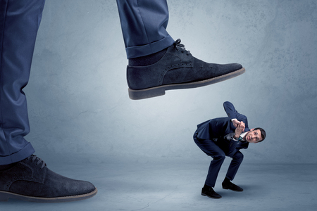 trampled: Young small businessman is trampled by a big foot in an empty space