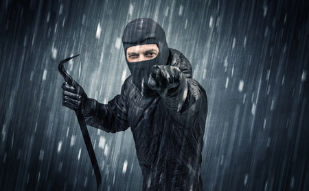 hijack: Burglar in action in black clothes with rainy concept. Stock Photo