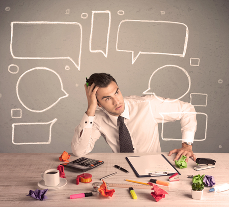 An intelligent elegant business person sitting at a desk and working with drawn empty text bubbles, boxes around him concept Stock Photo