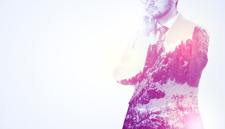resolving: Young businessman in suit standing with sunny snowy mountain and trees graphic.