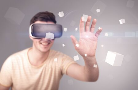 eyewear: Young impressed man wearing virtual reality goggles with grey cubes around him Stock Photo