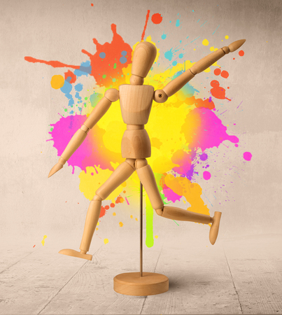 Wooden mannequin posed in front of a greyish background with colorful splashes behind it Stock Photo