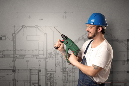 Worker standing with tool in his hand in front of technical drawings. Stock Photo