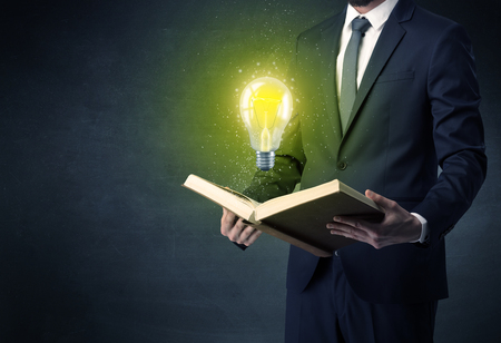Businessman holding book with bulb. Stock Photo
