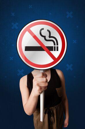 禁煙グラフィックなしの丸い印を保持しているカジュアルな若い女性