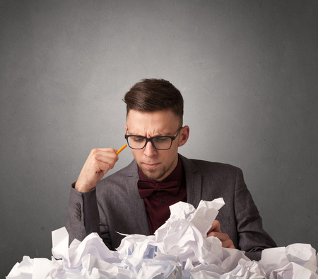 Young businessman sitting behind crumpled paper with grey background Stock Photo