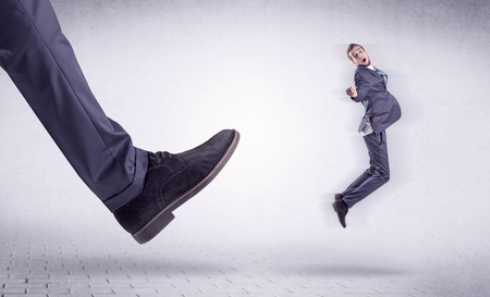 kicked out: Small young businessman kicked out by a big black shoe Stock Photo