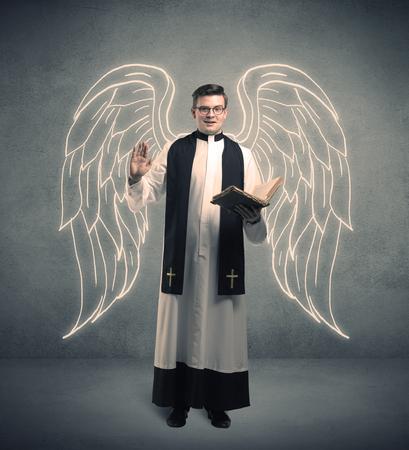 Un sacerdote varón joven con grandes alas de ángel extraídas de pie con la Santa Biblia en su concepto de manos. Foto de archivo - 79938427