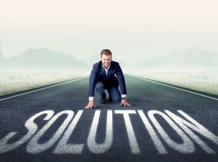 competitor: Young determined businessman kneeling before solution text Stock Photo