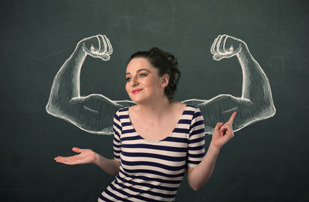 Pretty young woman with sketched strong and muscled arms photo