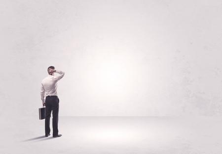 Elegante Geschäftsperson, die mit seinem zurück betrachtet großes leeres Leerraumkonzept steht Standard-Bild - 79933880