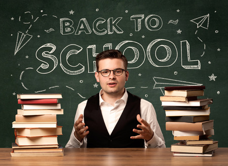 suspicion: A young teacher in glasses sitting at classroom desk with pile of books in front of blackboard saying back to school drawing concept.