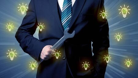 Better-looking businesman holding tool with idea bulbs concep Stock Photo
