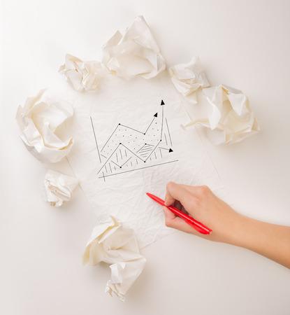 Female hand next to a few crumpled paper balls drawing a progress chart Stock Photo