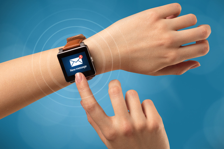 Female hand receives new message on her smartwatch Stock Photo