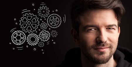 progressing: Portrait of a young businessman with rotating gears next to him on a dark background