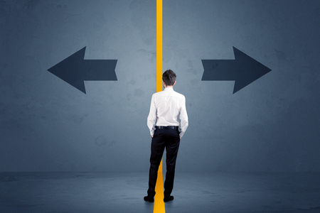 CHALLENGING: Business person choosing between two options separated by a yellow border arrow concept Stock Photo