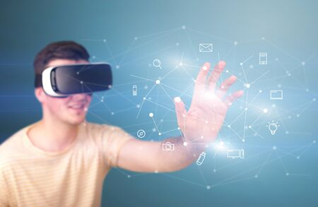 eyewear: Young impressed man wearing virtual reality goggles with mixed media icons around his finger Stock Photo