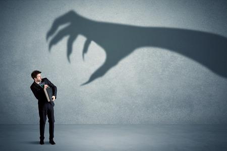przedsiębiorca boi wielkiego potwora pazur cienia koncepcji na tle Zdjęcie Seryjne