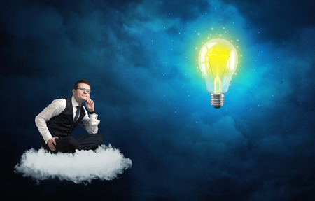Caucasian businessman sitting on a white fluffy cloud lookind and wondering at a big, shiny, glowing yellow lightbulb Stock Photo
