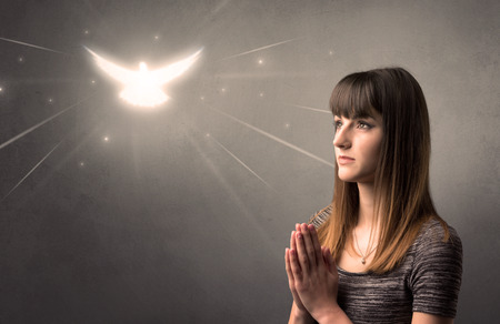 Young woman praying on a grey background with a sparkling bird above her