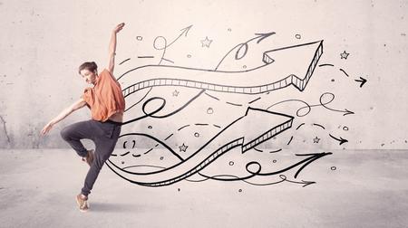 Un hip hop hermoso joven bailando danza contemporánea bailando en frente de la pared urbana de fondo gris con líneas y flechas concepto Foto de archivo - 80154679