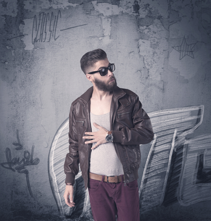funny bearded man: A handsome hipster guy with beard and sunglasses standing in front of an urban wall with graffiti concept Stock Photo