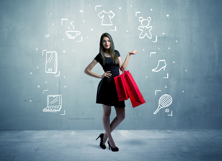 to spend: A beautiful young girl in black standing with red shopping bags in front of urban wall background and laptop, shoes, tennis icons concept
