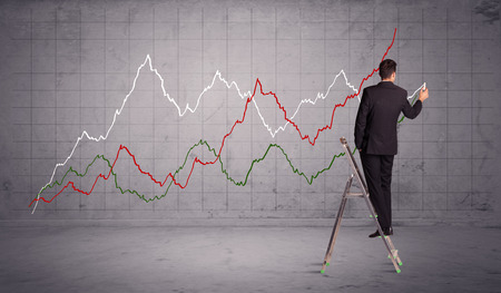 progressing: A guy in modern suit standing on a small ladder and drawing a chart on grey wall background with exponential progressing curves, lines
