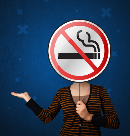 Casual young woman holding round sign with no smoking graphic Stock Photo