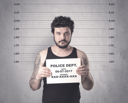 con man: Caught gangster in jail with table on his hand. Stock Photo