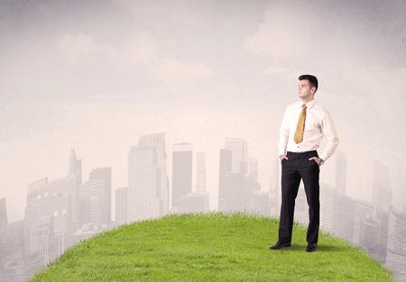 Een zekere mannelijke goed uitziende officemanager die zich in klein groen gras voor stadslandschap met lang gebouwenconcept bevindt.