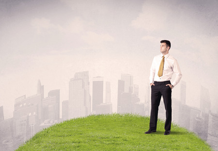 Ein überzeugter Mann Suche gut Büroleiter mit hohen Gebäuden Konzept vor Stadt-Landschaft im kleinen grünen Gras. Standard-Bild