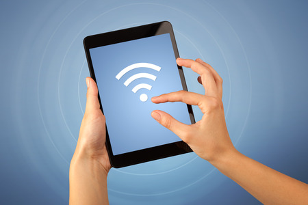 touching: Female fingers touching tablet with wireless connection icon Stock Photo