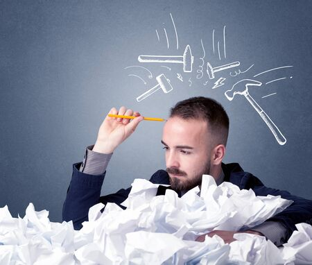 difficulties: Young businessman sitting behind crumpled paper with drawn hammers hitting his head