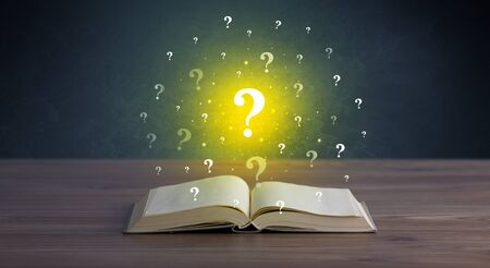 Yellow question marks hovering over open book Zdjęcie Seryjne