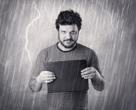Caught gangster with rainy, grey background and black table on his hand. Stock Photo
