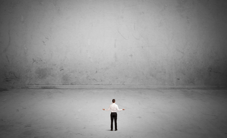 considering: A tiny elegant businessman standing in large empty urban space with concrete walls and grey background concept