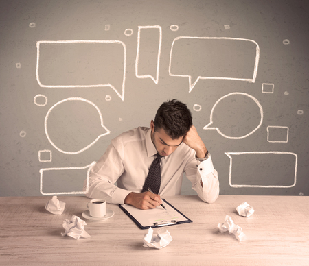 exhausting: An intelligent elegant business person sitting at a desk and working with drawn empty text bubbles, boxes around him concept Stock Photo